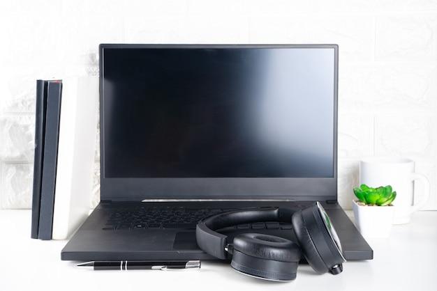 Scrivania da ufficio semplice. laptop, cuffie e tazza di caffè o tè