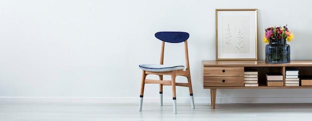 Pittura semplice e fiori colorati freschi in vaso di vetro posto su un armadio in legno con libri in piedi accanto alla sedia bianca e blu. incolla qui la tua tabella