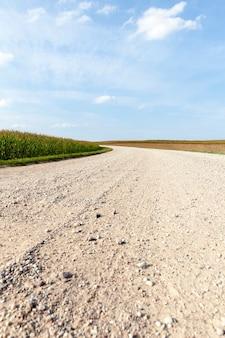 Semplice strada rurale sabbiosa percorsa dai mezzi di trasporto, cielo blu sullo sfondo