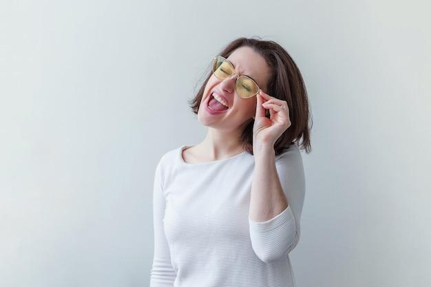 Semplice ritratto in studio di moda hipster, sorridente ragazza bruna dai capelli corti in occhiali da sole gialli alla moda isolati su bianco