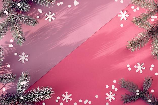 Sfondo invernale semplice. rametti di abete su carta rosa bicolore con coriandoli.