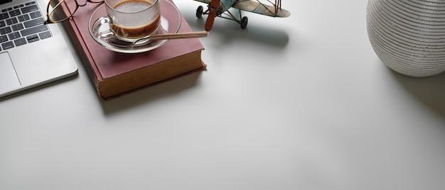 Semplice area di lavoro con copia spazio, laptop, libro, tazza di caffè, bicchieri e decorazioni