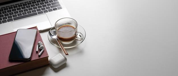 Area di lavoro semplice con copia spazio, laptop, tazza di caffè, libro, smartphone e auricolare wireless