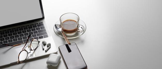 Semplice area di lavoro con copia spazio, laptop, tazza di caffè, auricolari, smartphone e occhiali da vista