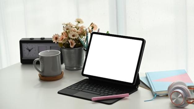 Area di lavoro semplice con tablet schermo vuoto, notebook, cuffie, tazza di caffè e vaso di albero sul tavolo bianco.