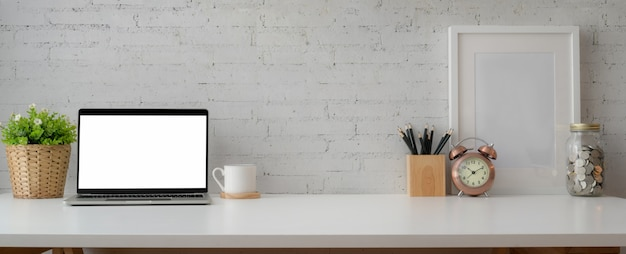 Semplice spazio di lavoro con laptop, articoli di cancelleria, decorazioni e spazio di copia