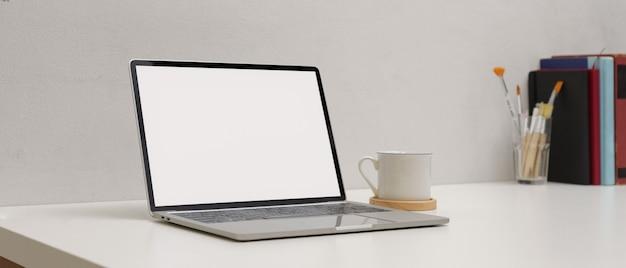 Semplice area di lavoro con mock up laptop, tazza, copia spazio pennelli e libri sul tavolo bianco