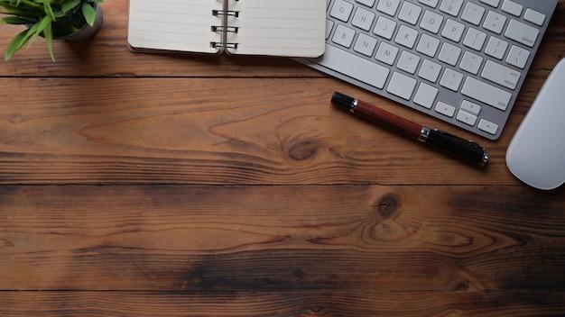 Area di lavoro semplice con notebook, pianta d'appartamento e tastiera su tavolo di legno.