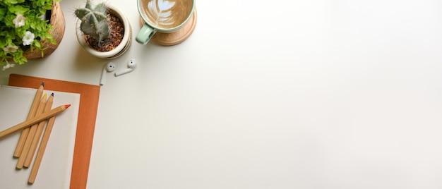 Area di lavoro semplice con vaso della pianta della tazza della cancelleria e spazio della copia sulla scrivania bianca
