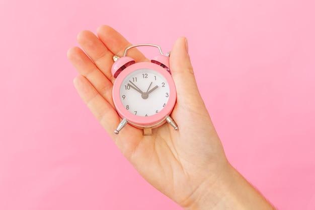 Progettare semplicemente la mano femminile della donna che tiene la sveglia del campanello gemello che suona isolata sul tavolo rosa