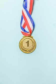 Vincitore del design piatto semplicemente piatto o medaglia del trofeo d'oro campione isolato su sfondo colorato blu vic ...