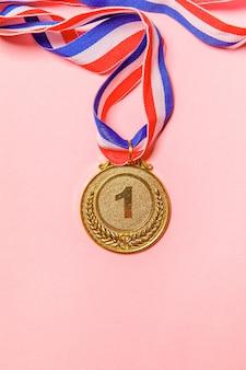 Vincitore del design semplicemente piatto o campione medaglia d'oro del trofeo isolato su sfondo colorato rosa. vittoria primo posto della competizione. concetto vincente o di successo. spazio di copia vista dall'alto.
