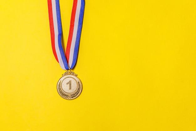 Vincitore del design semplicemente piatto o medaglia del trofeo d'oro campione isolato su sfondo giallo colorato v ...