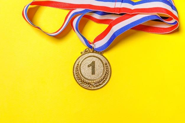 Vincitore del design piatto semplicemente piatto o medaglia del trofeo d'oro campione isolato su sfondo giallo colorato. vittoria primo posto della competizione. concetto vincente o di successo. spazio di copia vista dall'alto.