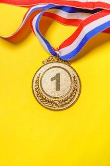 Vincitore del design semplicemente piatto o medaglia del trofeo d'oro campione isolato su sfondo giallo colorato