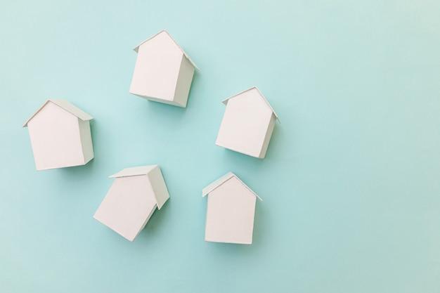 Design semplice e piatto con case modello giocattolo bianche in miniatura isolate su sfondo blu pastello. concetto di casa da sogno di assicurazione di proprietà ipotecaria. spazio di copia vista dall'alto piatto.