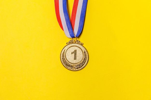 Semplicemente piatto laico vincitore o campione medaglia trofeo d'oro isolato su sfondo colorato giallo.