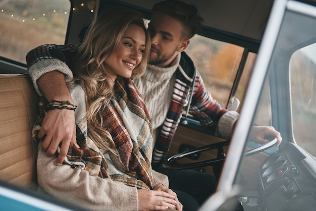 Semplicemente innamorato. bella giovane coppia che si abbraccia e sorride mentre è seduta in un mini furgone in stile retrò