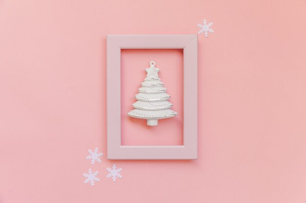 Albero di abete composizione semplicemente minima nel telaio rosa isolato su sfondo rosa