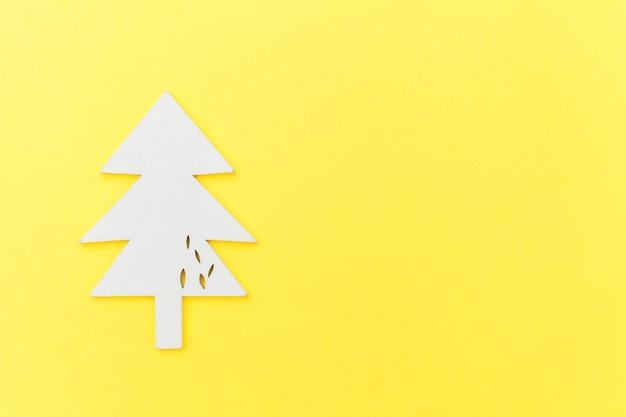 Semplicemente composizione minima albero di abete ornamento oggetto invernale isolato su sfondo giallo alla moda