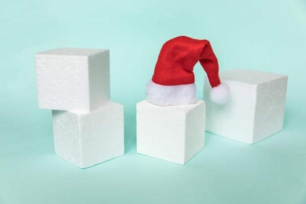 Composizione semplicemente minimale oggetto invernale cappello da babbo natale e forme cubiche forma geometrica podio isolato bl...