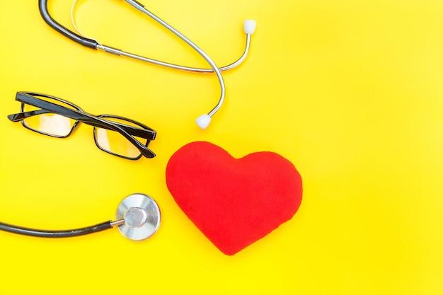 Design semplicemente minimale con stetoscopio o occhiali per fonendoscopio e cuore rosso isolato su giallo alla moda