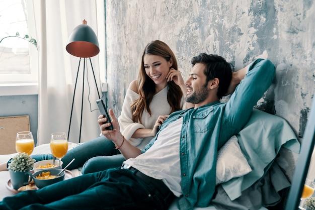 Semplicemente riposando. bella giovane coppia che fa colazione mentre trascorre il tempo a letto a casa