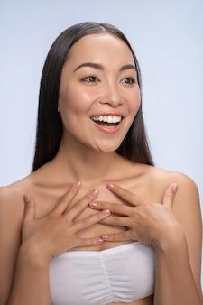 Emozioni sincere. carina donna dai capelli lunghi che mantiene il sorriso sul viso, contenta delle buone notizie
