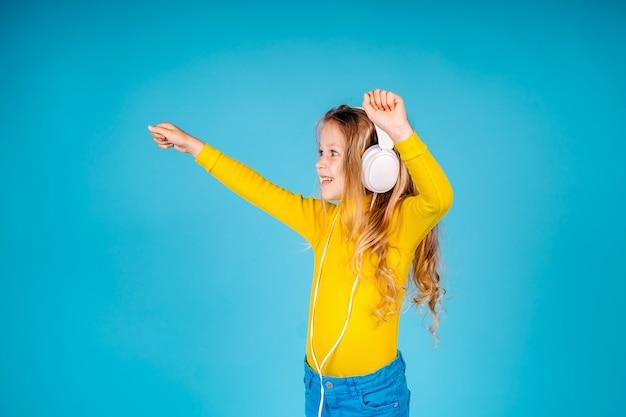 Canta felicità. il bambino felice indossa le cuffie. piccolo fan della musica. bambina felice. la bambina ascolta la musica isolata. divertirsi.