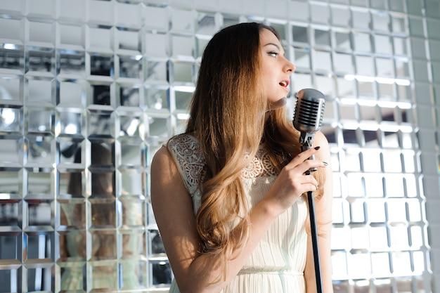 Cantante davanti a un microfono. festa karaoke. ragazza di bellezza con un microfono che canta. festa in discoteca. celebrazione.
