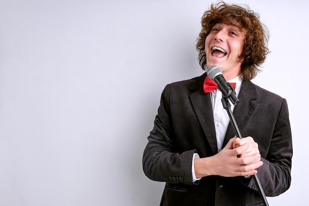 Cantante che canta espressivo nel microfono vocale, cantante di musica classica. muro bianco isolato