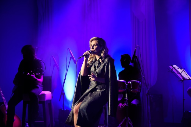 Cantante con microfono sul palco in fase di illuminazione.
