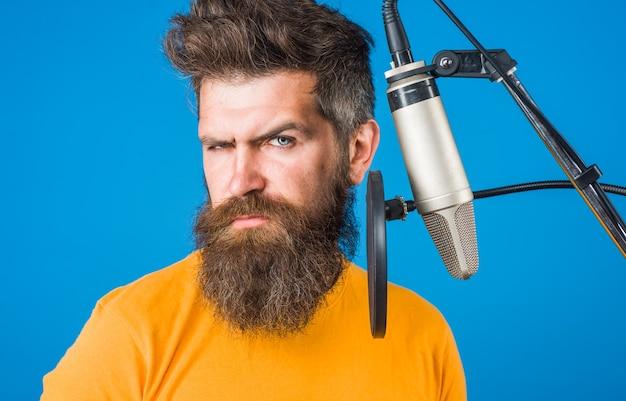 Cantando. uomo barbuto al karaoke. uomo che canta con un microfono. microfono. canta una canzone in un microfono. serata karaoke.