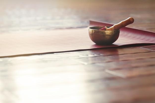 Una ciotola di canto si erge su un tappetino da yoga su un pavimento di legno con spazio per le copie terapia del suono e rilassamento