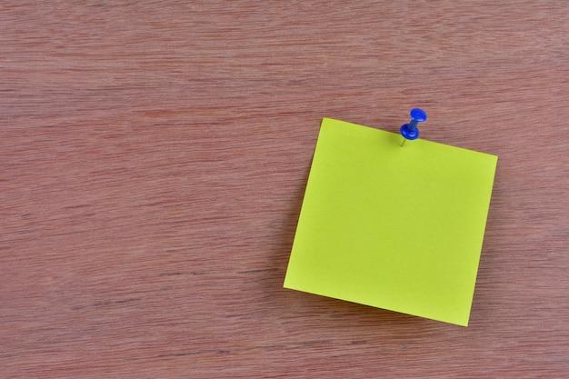 Carta per appunti bianca singola attaccata a una parete di legno