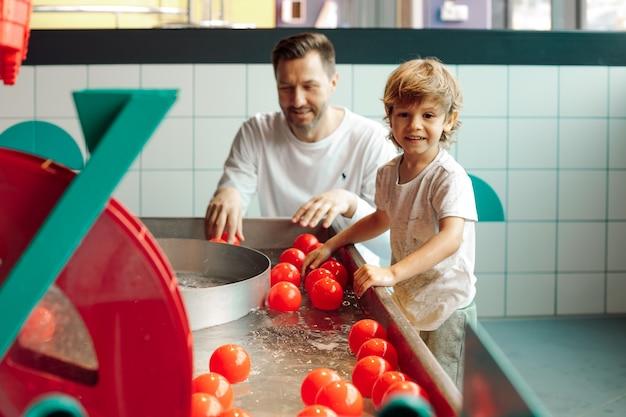 Il padre single gioca con suo figlio nel centro di intrattenimento per bambini con palline che galleggiano sull'acqua. imparare attraverso il gioco. infanzia. giochi educativi. comunicazione con il bambino.