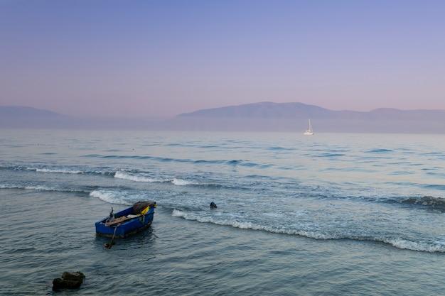 Singolo peschereccio che galleggia in acqua di mare