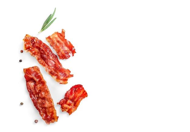 Fette di pancetta croccante fritte singole e rametto di rosmarino isolato su bianco