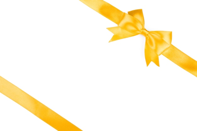 Singolo fiocco regalo, raso dorato, con nastri incrociati isolati su bianco Foto Premium