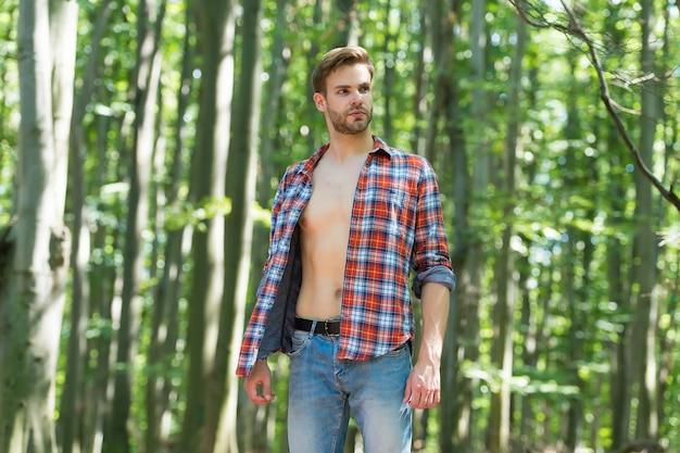 Singolo bel ragazzo con il torso nudo sexy in camicia aperta stile casual stare nei boschi il paesaggio naturale della giornata estiva di sole, uomo.
