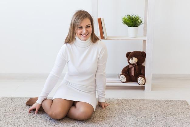 Singola giovane donna felice seduta su un pavimento di una stanza vuota, pensando a qualcosa