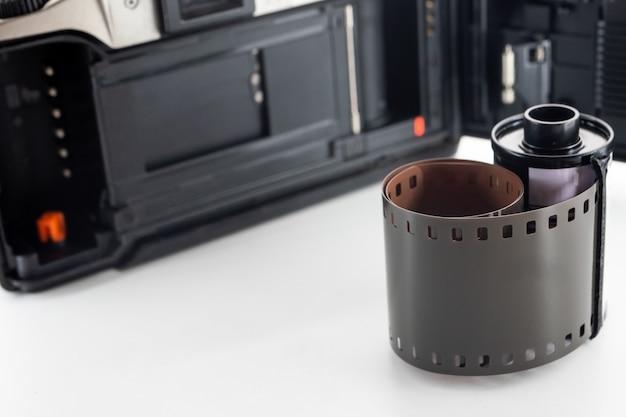 Fotocamera reflex a obiettivo singolo e un rotolo di pellicola su uno sfondo bianco.