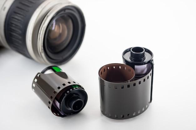 Rotoli di pellicola e pellicola reflex con obiettivo singolo su uno sfondo bianco.