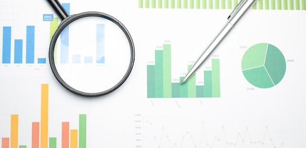 Lente d'ingrandimento singola con manico nero, appoggiata ai dati finanziari. concetto di ricerca aziendale e finanziaria.