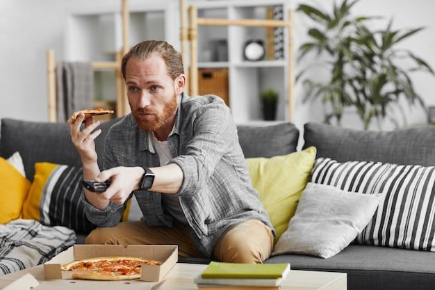 Single man eating pizza mentre si guarda la tv