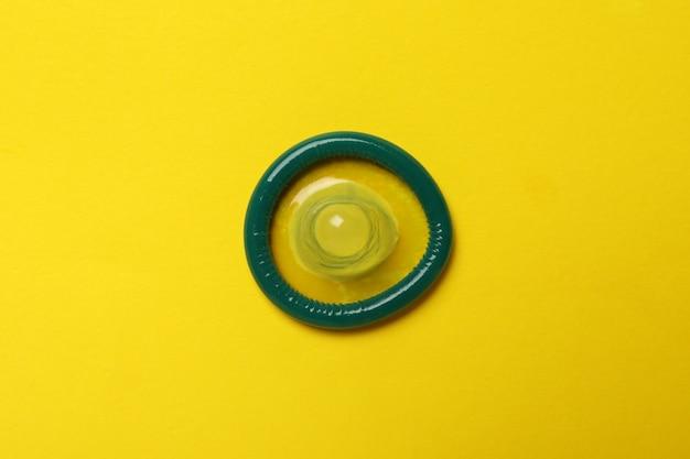 Preservativo di menta singolo sulla parete gialla, vista dall'alto