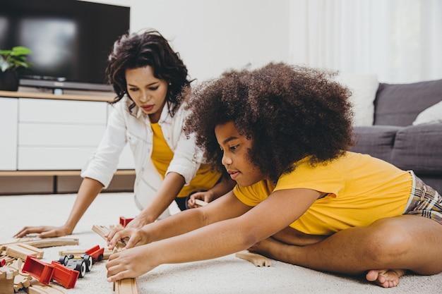 Mamma single che vive con due figlie che imparano e giocano a puzzle nell'appartamento di casa. tata in cerca o assistenza all'infanzia in soggiorno per i neri.