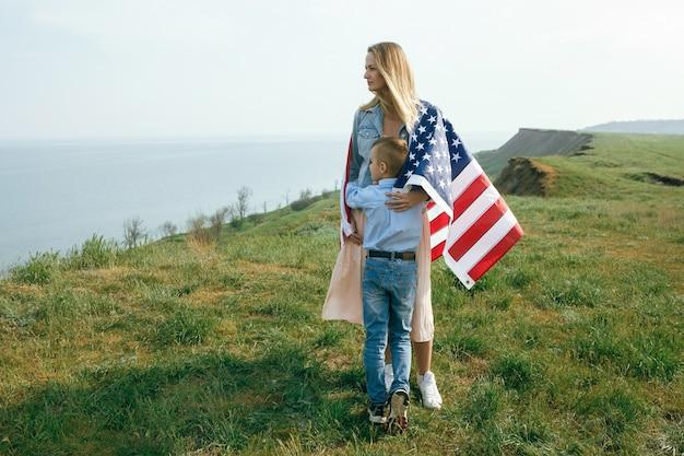 Madre single con figlio il giorno dell'indipendenza degli stati uniti. la donna e il suo bambino camminano con la bandiera usa sulla costa dell'oceano
