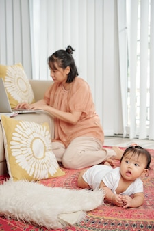 Madre single che lavora al computer portatile