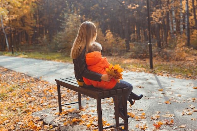 La madre single genitore e il bambino in autunno nel parco si siedono sulla panchina. stagione autunnale e concetto di famiglia.
